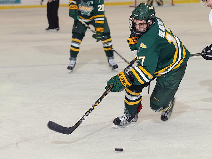 Men's hockey player Mitchell Herlihey skates with the puck