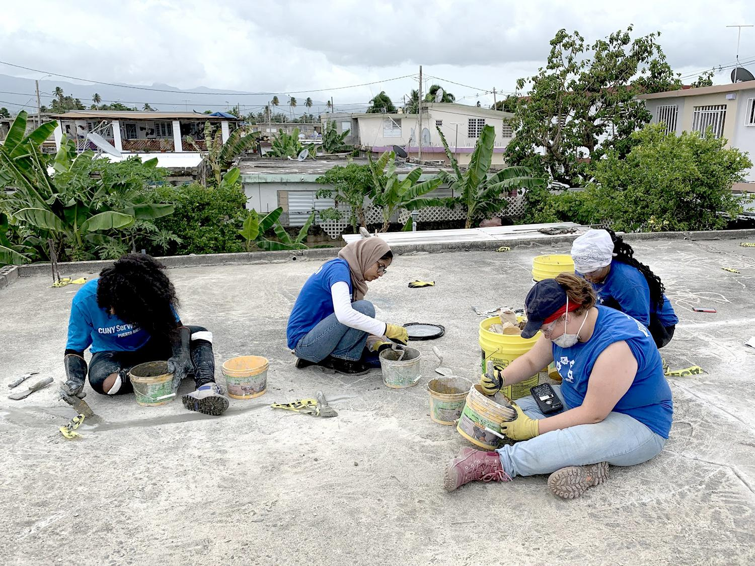 Students work on patching a roof in Puerto Rico