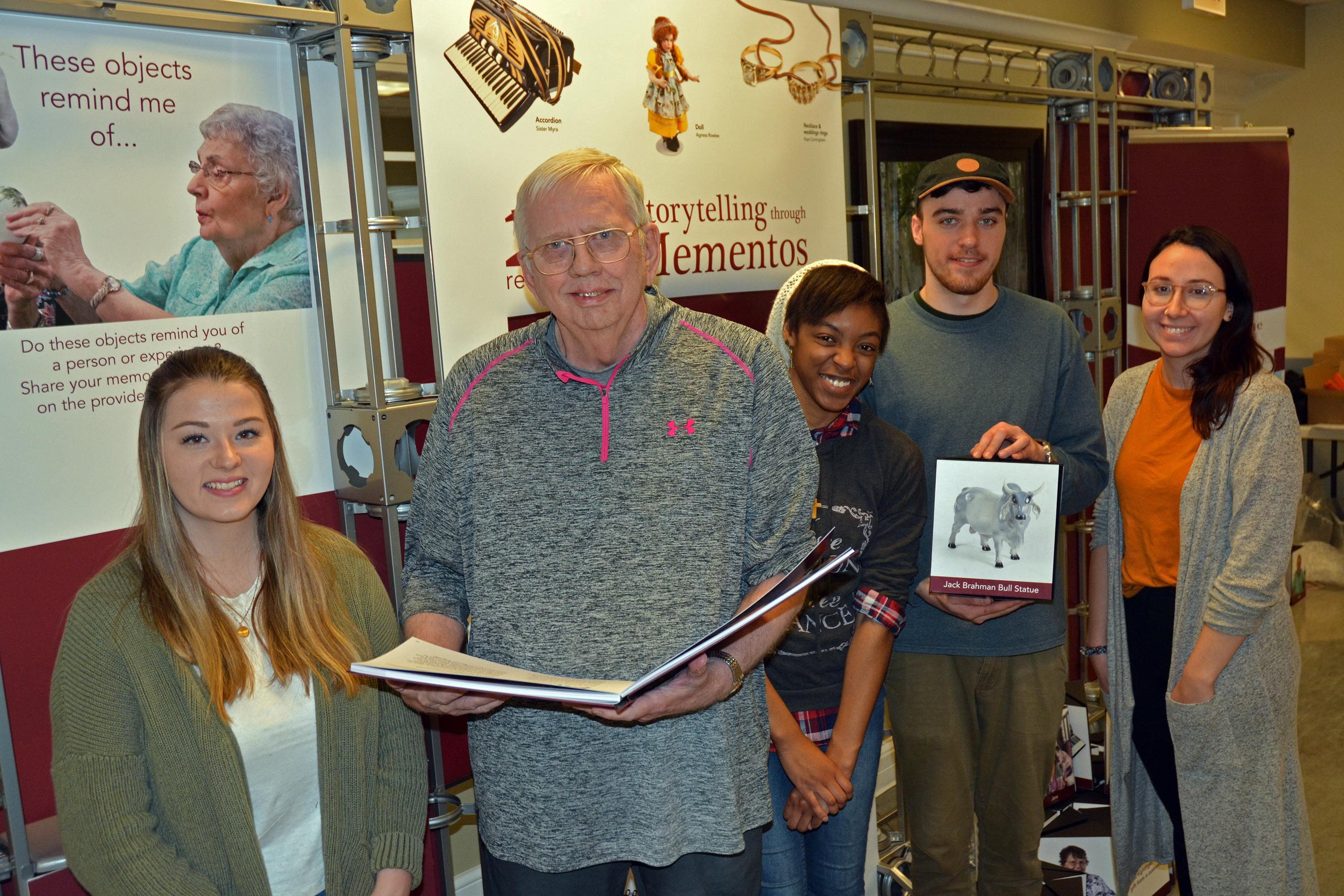 Students and a senior citizen with items from Recollections art exhibition