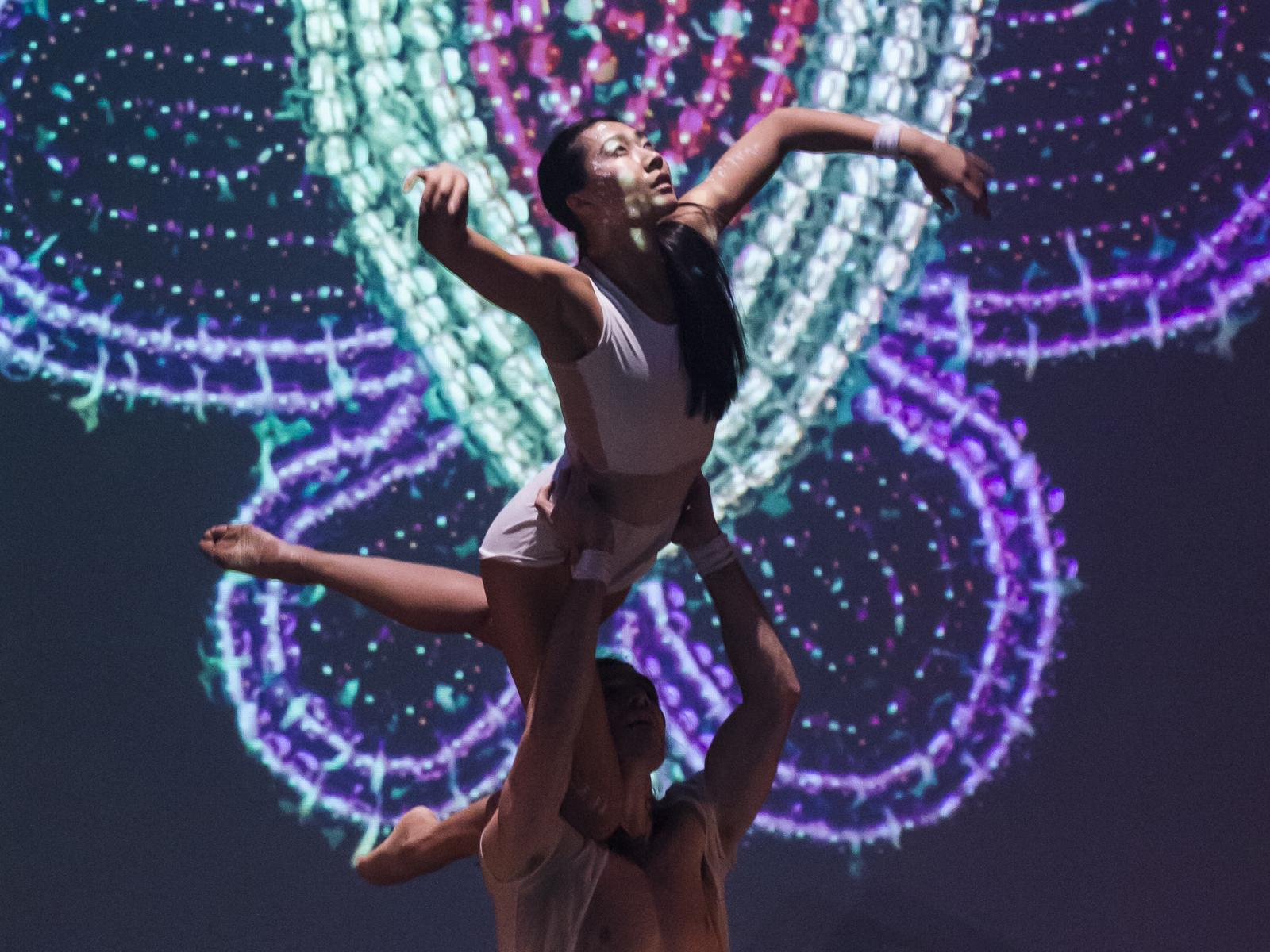 A dancer soars with a lighted backdrop in a Red Sky Performance piece
