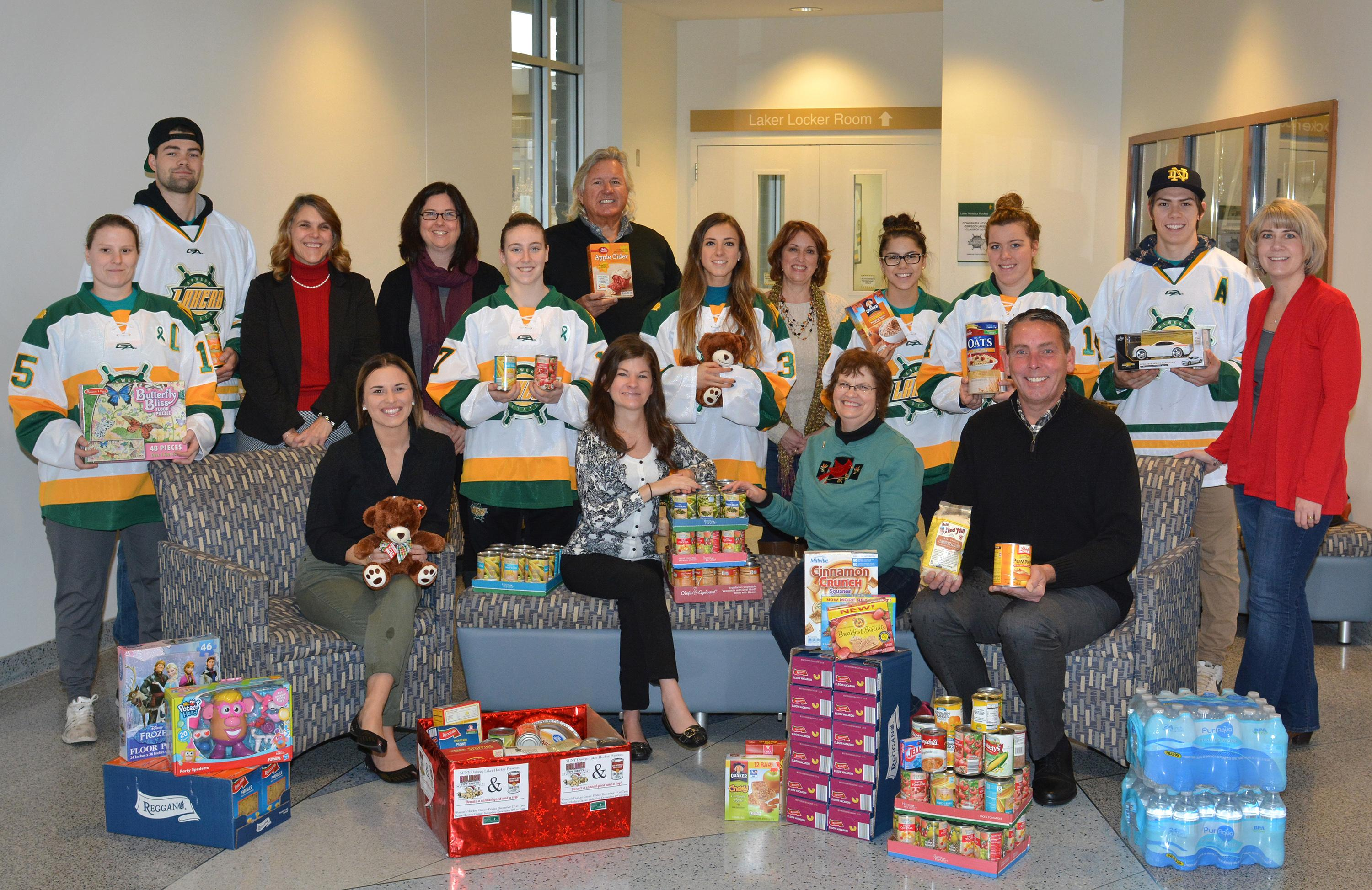 Hockey players, Oswego employees, and representatives of United Way and Human Concerns Center with food and toys