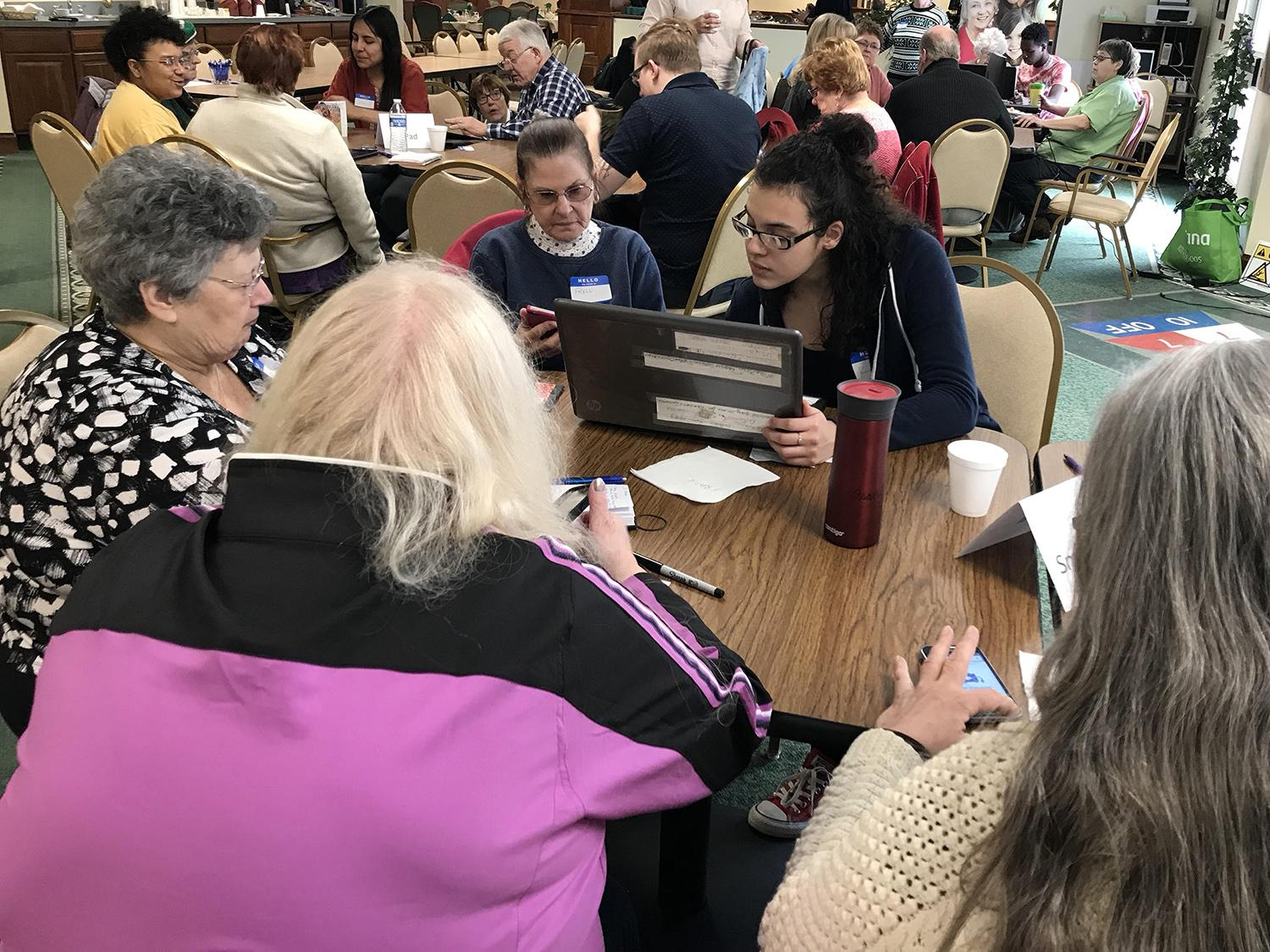 Students help senior citizens with technology questions