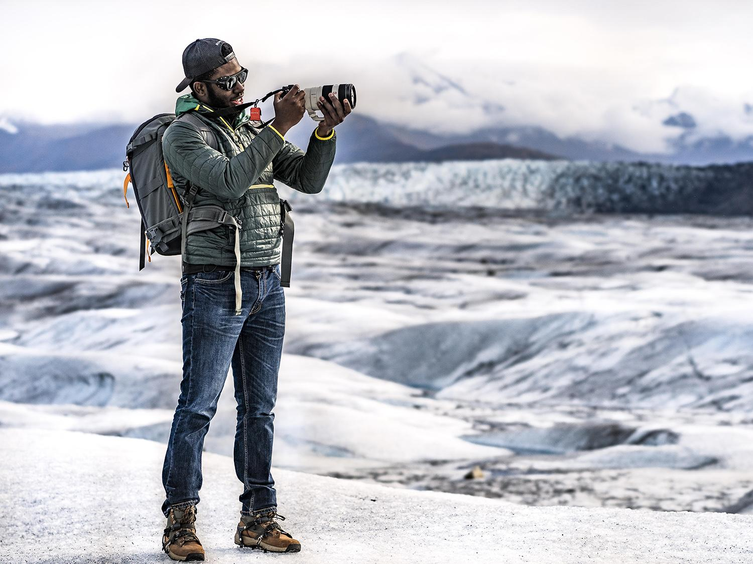 Mic-Anthony Hay looks through a camera with an arctic scene in background