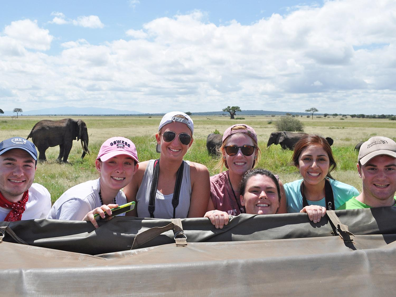 Students pose with elephants in background