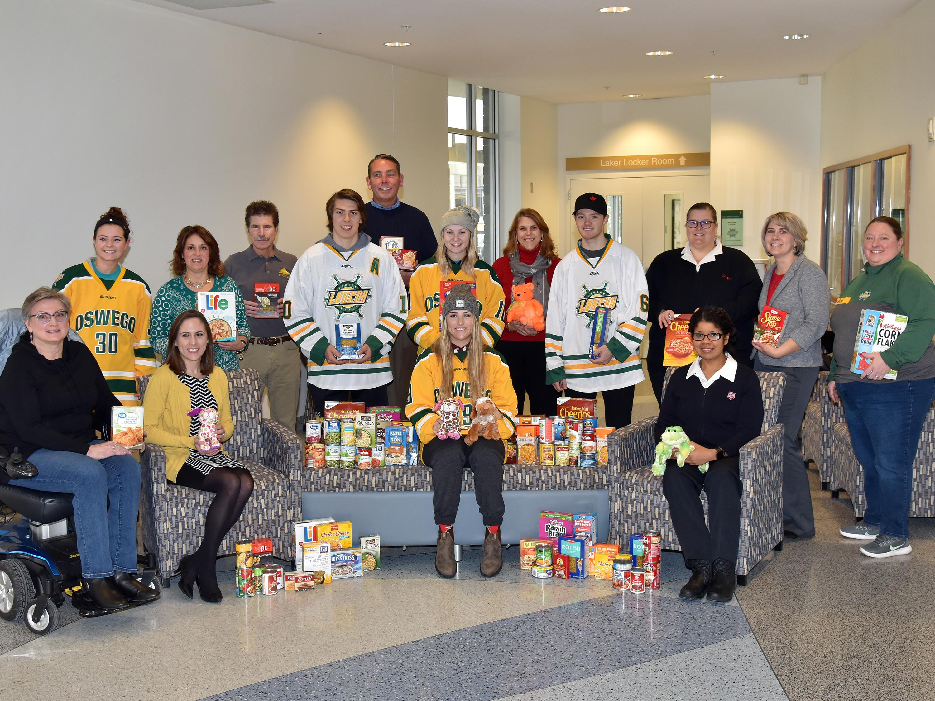 Laker hockey players with United Way and campus organizers collecting toy and food donations
