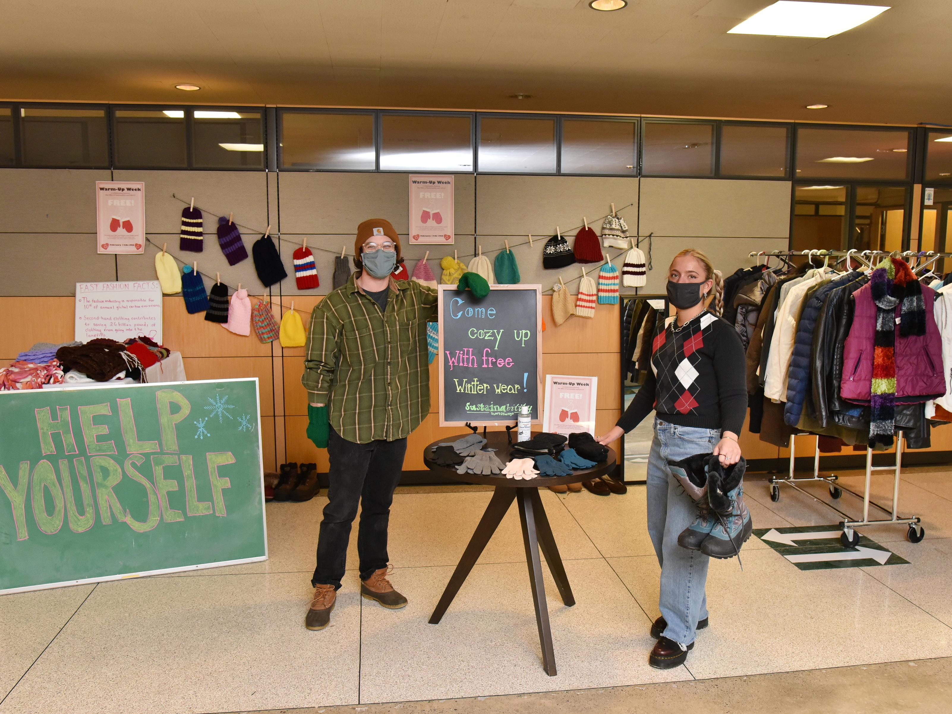 Sustainability Office students showing off coats, boots, hats, gloves and scarves available for free