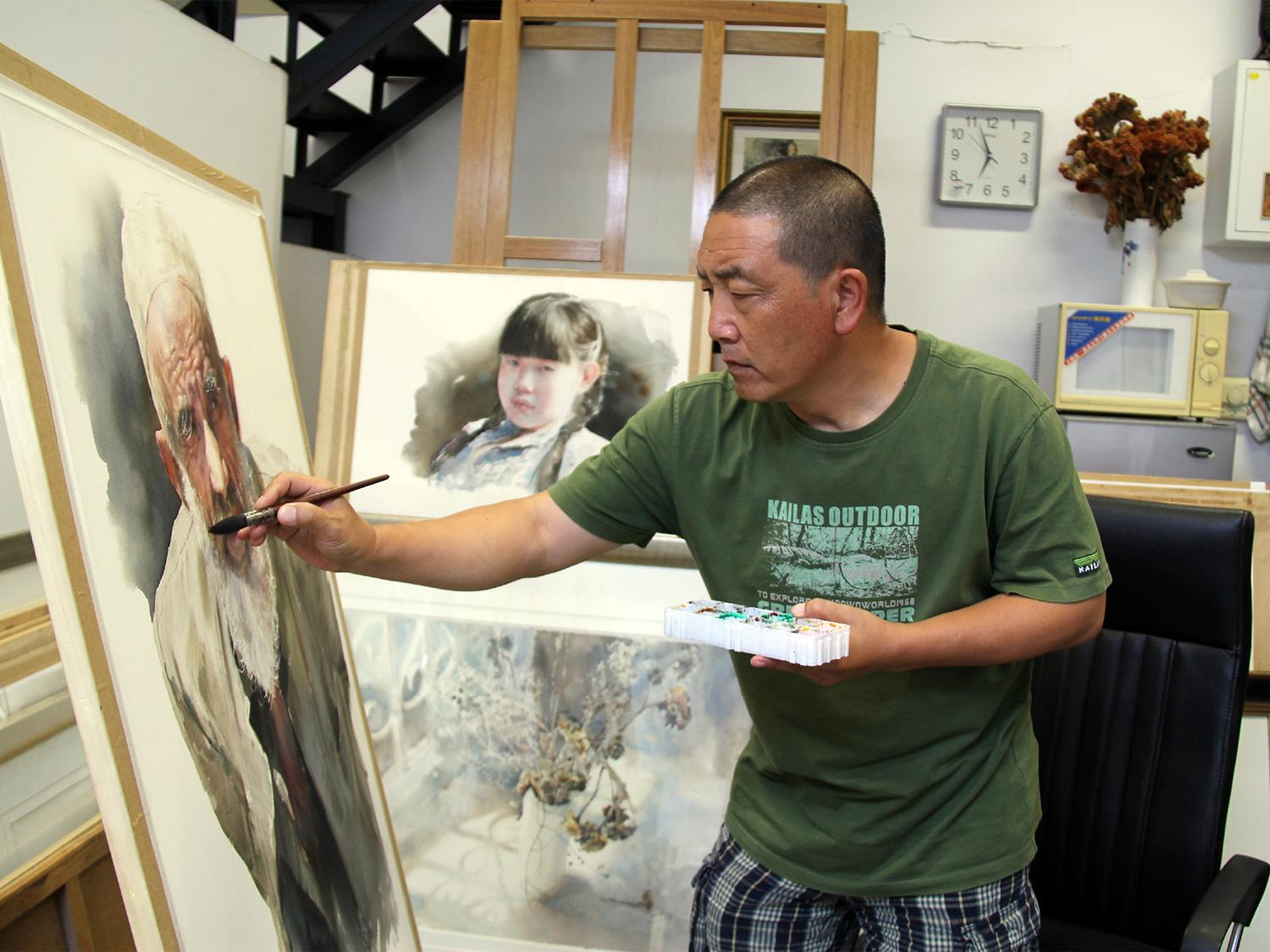 Artist Zhinan Jiang works on a watercolor painting