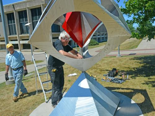 Artist Bob Turan with his sculpture that features a pinwheel in a box upon a pyramid