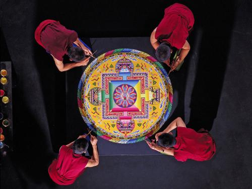 Tibetan monks of the Drepung Loseling Monastery work on sand art painting