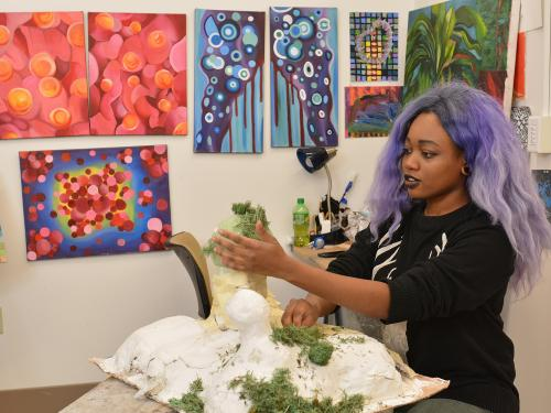 Star Daniels applies moss to a sculpture
