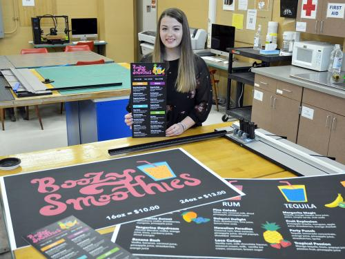 Art student Julie Farquhar poses with pieces from her portfolio