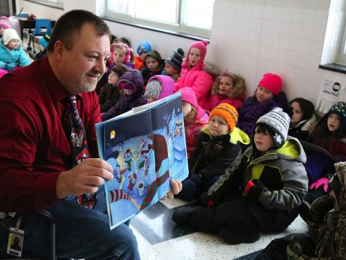 Sandy Creek Elementary School Principal Tim Filiatrault shares a book with young readers