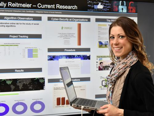 Holly Reitmeier with cybersecurity research poster