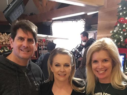 Juliet Giglio, her husband Keith and star Melissa Joan Hart on set of their Hallmark movie Christmas Reservations
