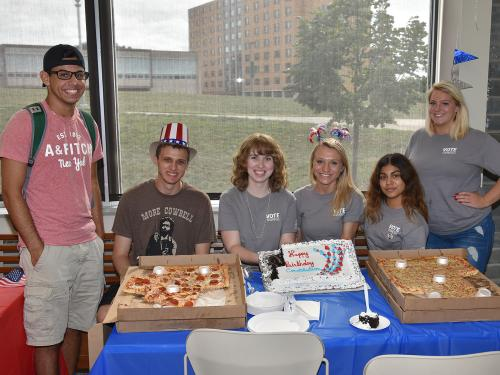 Students with pizza and cake at Constitution Day party in 2018