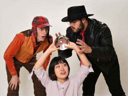 Rehearsal image of performers trying to discern the future via a crystal ball