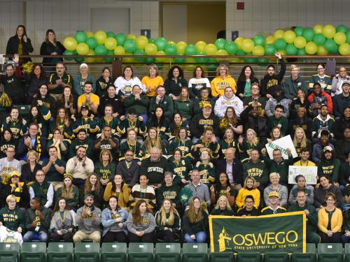 Group of students, faculty, staff and alumni in green and gold
