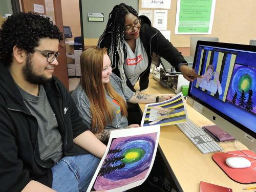 Students look at artwork submitted by schoolchildren