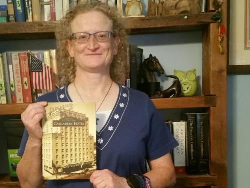 Political science faculty member Helen Knowles holds book on Cascadian Hotel
