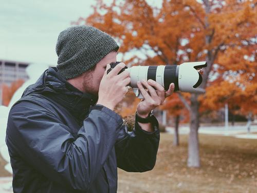 Kyle Hurley taking a photograph for the Oswego Photo Showcase project.
