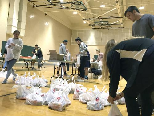 Laker student-athletes packing bags of food