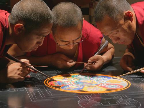 Monks work on creating mandala, beautiful sand art