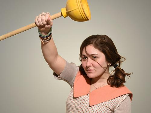Michaela Buckley dancing while holding a plunger