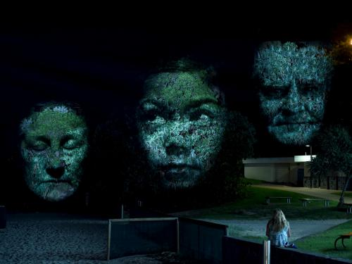 Three projected faces appear on trees in a previous installation of Craig Walsh's Monuments