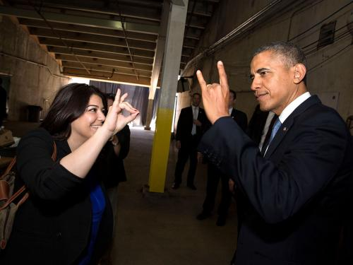 President Barack Obama's Personal Secretary Ferial Govashiri shows him how to make the sign of the anteater, mascot of the University of California, Irvine, prior to the UCI commencement at Angels Stadium in Anaheim, Calif., Saturday, June 14, 2014.