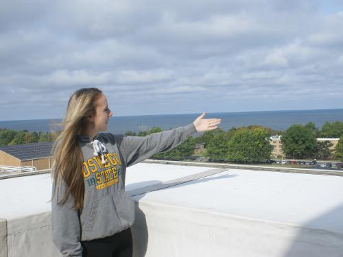 Student tour guide gestures and lake and campus