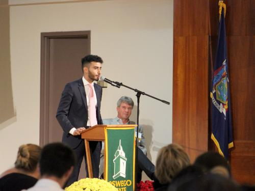 Ahmed Albajari, at podium, was selected to speak on behalf of all scholarship students at the annual SUNY Oswego Scholars Breakfast