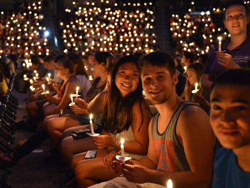 Students with lit candles at the Opening Torchlight Ceremony