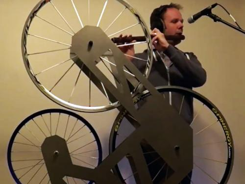 Music faculty member Paul Leary with instrument that combines flute with bicycle wheels