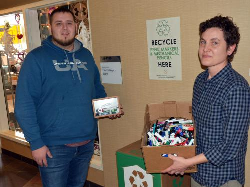 Kate Spector and student assistant Connor Haney prepare to feed used writing implements to a TerraCycle zero waste recycling box