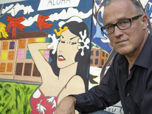 Ron Throop with a painting on Roy Lichtenstein's time in Oswego