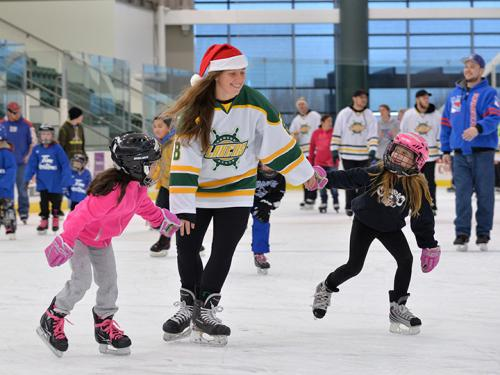 Two little girls skate with a women's hockey player