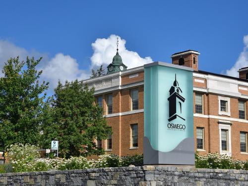SUNY Oswego sign with background of Sheldon Hall