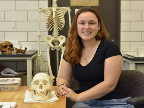 Hannah Kruse with a skull in a forensic lab