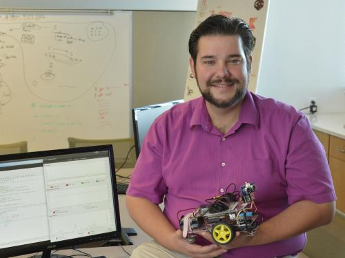 Computer science faculty member Bastian Tenbergen holds a small robotic car in his office