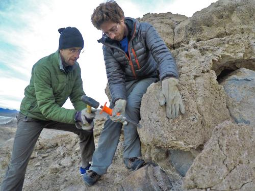 Faculty member Justin Stroup helps collect rock samples on a mountain