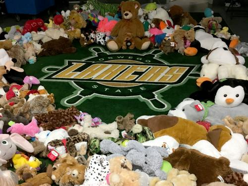 Stuffed animals ring a Lakers wheel logo in a hockey locker room