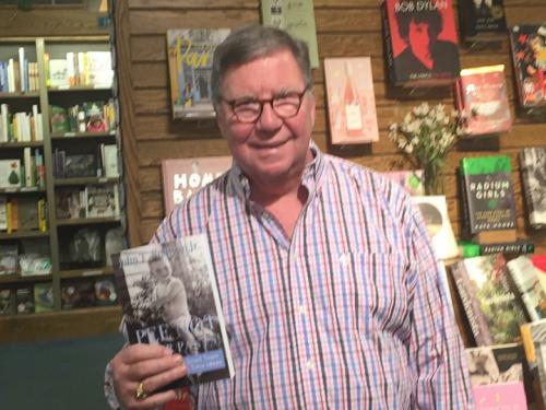 John Sullivan holding a book with many of his stories