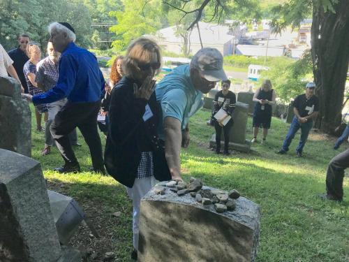 Former European refugees and families walk through a cemetery in Fort Ontario