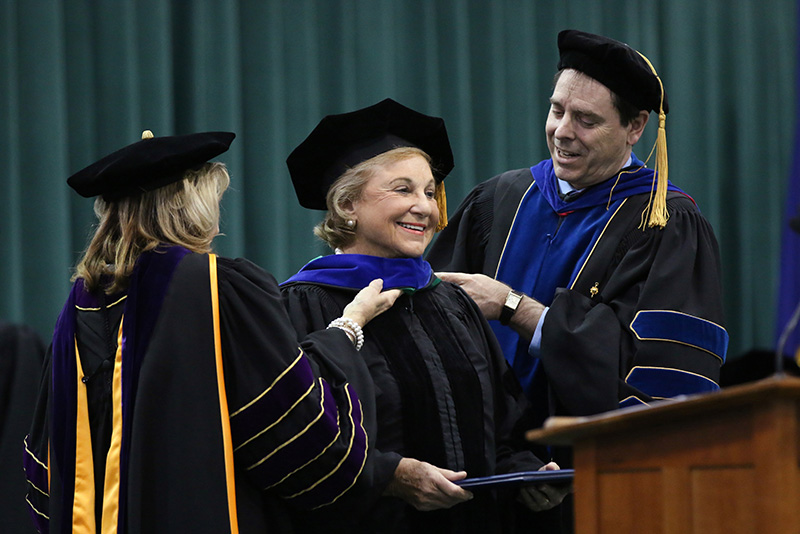 College President Deborah F. Stanley (left) and Provost Scott Furlong arrange the hood of community leader and philanthropist Noreen Reale Falcone, recipient of SUNY's doctorate in humane letters