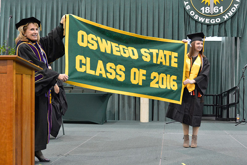 College President Deborah F. Stanley accepts the class banner from graduating senior Emily Pease