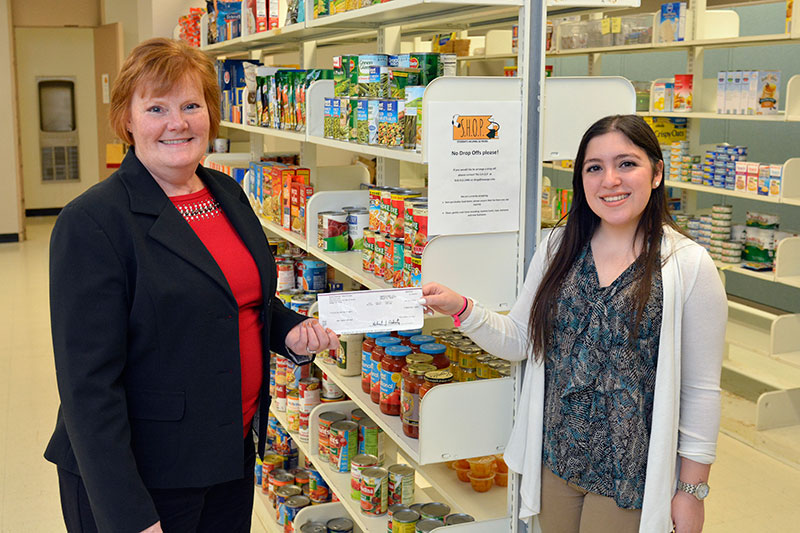 Student donating funds to S.H.O.P.