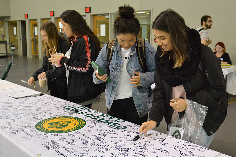 Students sign Class of 2017 banner at Grad Fair