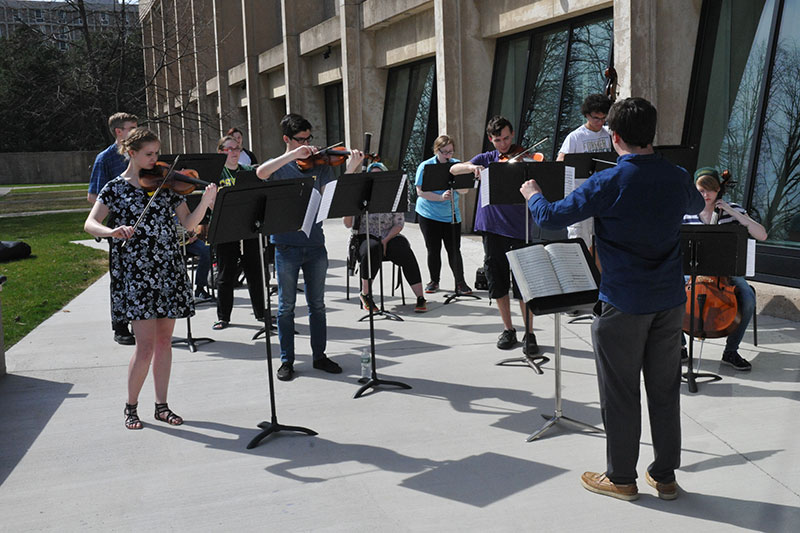 Lab orchestra practices outdoors