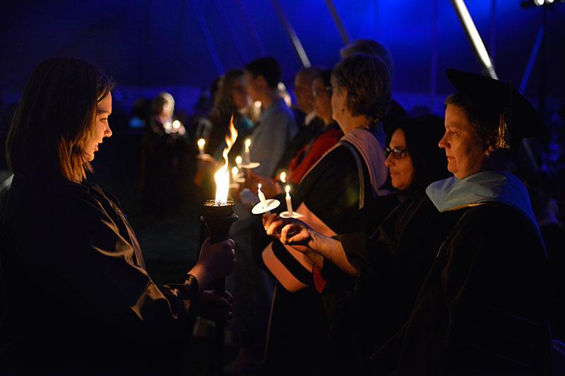 Torchlight participants light candles