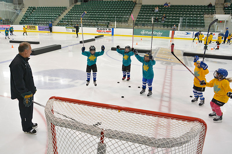 Coach Ed Gosek with young hockey players